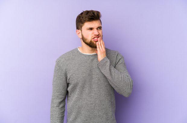 Aphthen: Ursachen, Dauer und Behandlung. Junger Mann mit Hand vor Mund und schmerzverzehrtem Gesicht