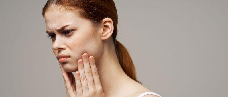 schöne Frau, die das Gesicht mit der Hand berührt, Zahnschmerzen, rotes Haar, weißes T-Shirt