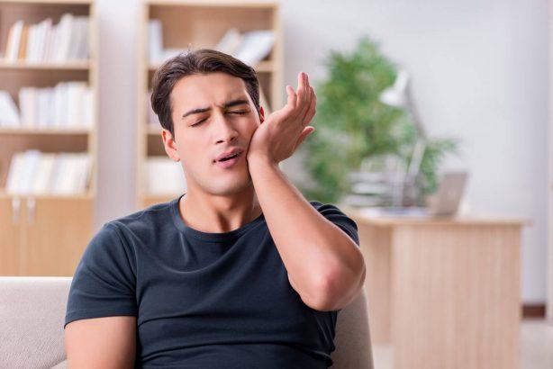 Junger attraktiver Mann mit Kieferschmerzen