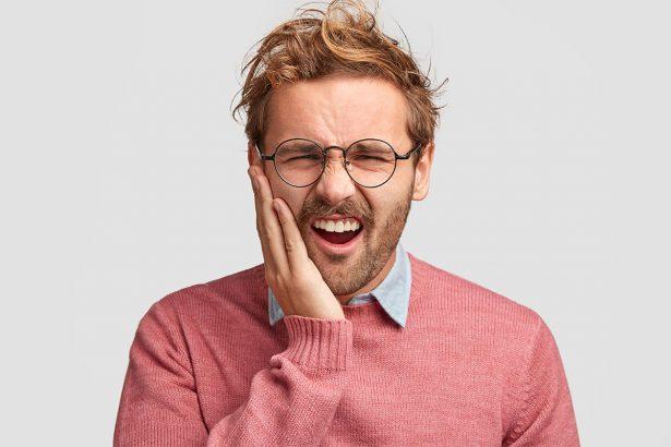 Junger Mann mit rosafarbenem Pullover fasst sich an die Wange und guckt schmerzverzerrt wegen seiner Phantomschmerzen