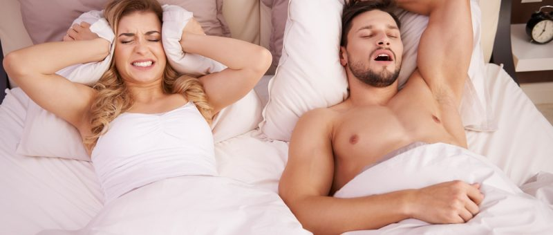 Junges Pärchen im gemeinsamen Bett, junge Frau kann aufgrund des Schnarchens ihres Partners nicht schlafen und hält sich ein Kissen an die Ohren