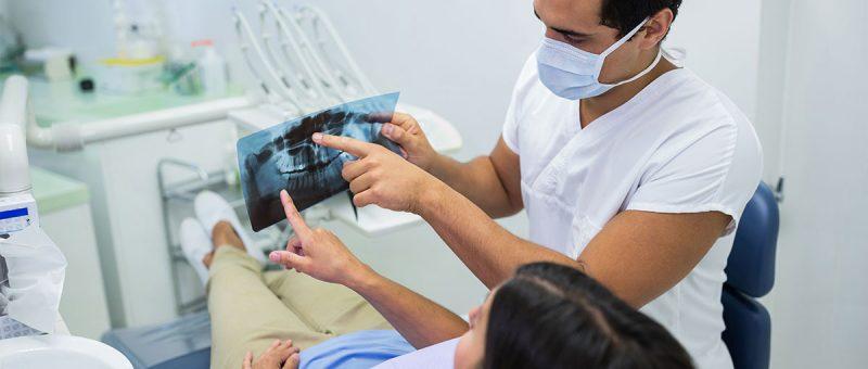 Wurzelspitzenresektion: Junger Zahnarzt zeigt Patienten eine Röntgenaufnahme und zeigt auf Zahnwurzel