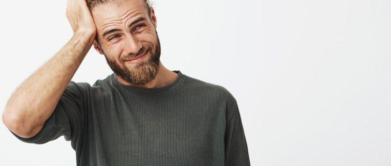 Junger blonder Mann leidet unter Kopfschmerzen durch Zahnschmerzen