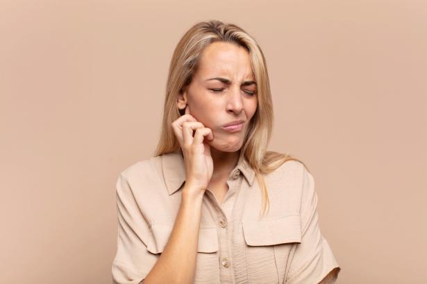 Junge Blonde Frau mit Schmerzen aufgrund einer Zahnwurzelentzündung