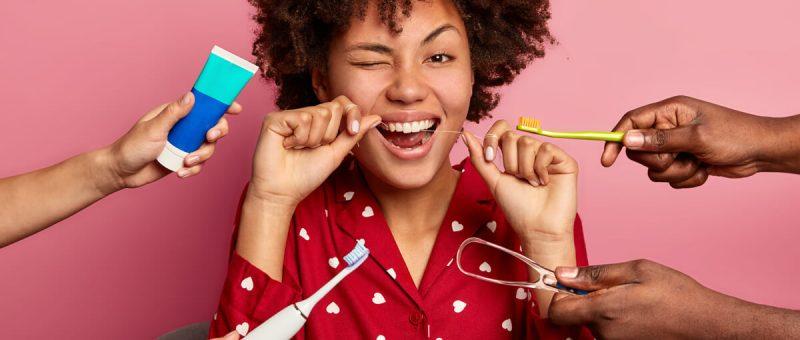 Glückliche lockige junge Frau verwendet Zahnseide, um ihre Zahnzwischenräume zu reinigen und kümmert sich um die Mundhygiene, umgeben von Zahnpasta, elektrischer Zahnbürste und Zungenreiniger